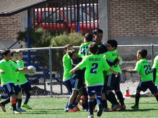 Los jugadores del Colegio Americano celebran con su entrenador tras ganar el Campeonato.