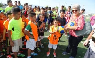 La señora Leticia Rodríguez entrega en forma simbólica uno de los balones a un jugador del Deportivo León.