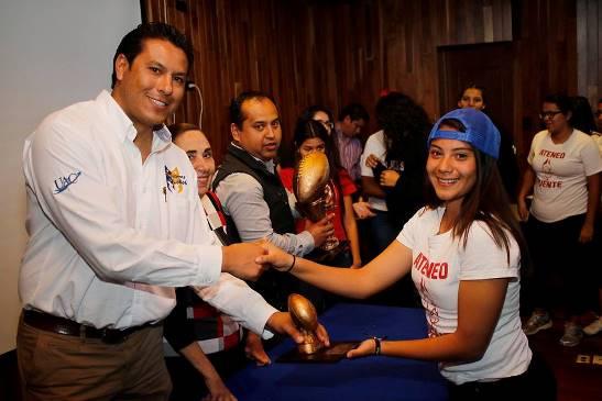 Una deporista del Ateneo Fuente es premiada por David Hernández Barrera, coordinador general del deporte de la UAdeC.