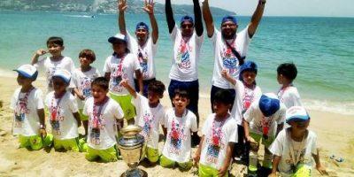 Los jugadores y entrenadores del Colegio México con la Copa de Campeones en la playa de Acapulco.